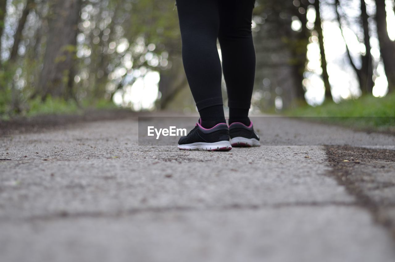 Low Section Of Woman Wearing Sport Shoes Standing On Road