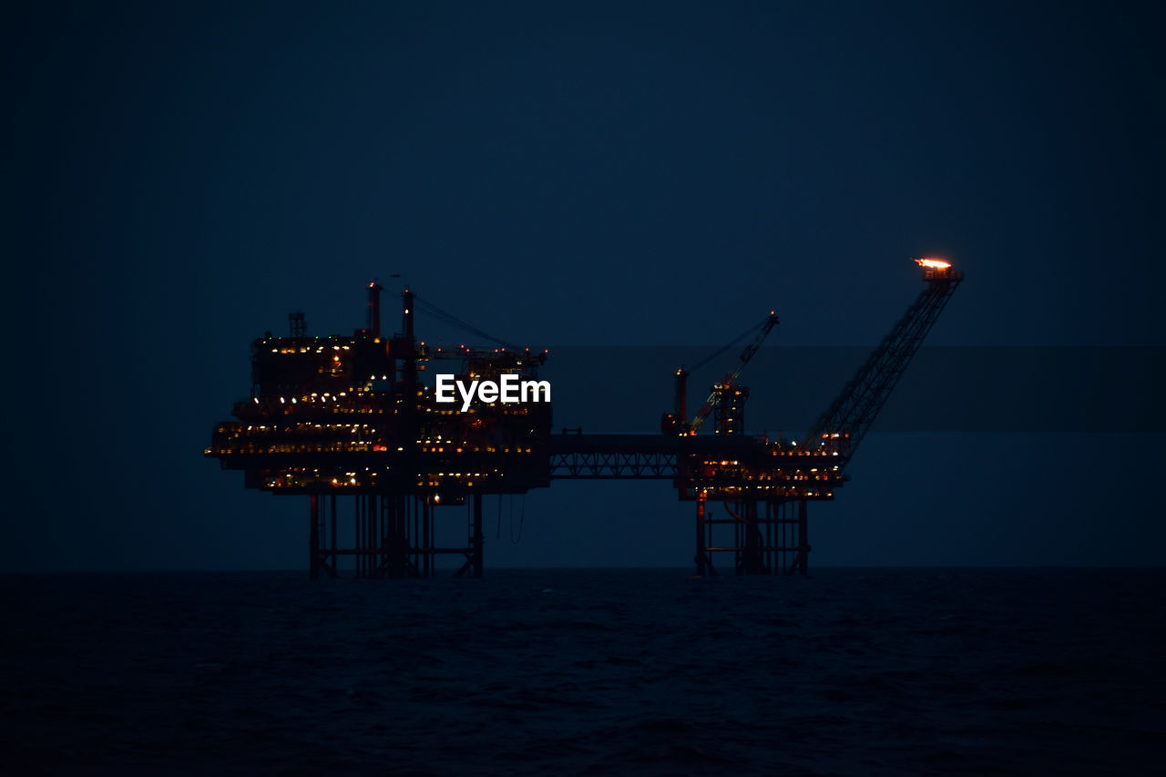 illuminated, sky, water, sea, drilling rig, industry, nature, oil industry, fuel and power generation, crane - construction machinery, offshore platform, machinery, clear sky, no people, waterfront, architecture, outdoors, blue, night, industrial equipment