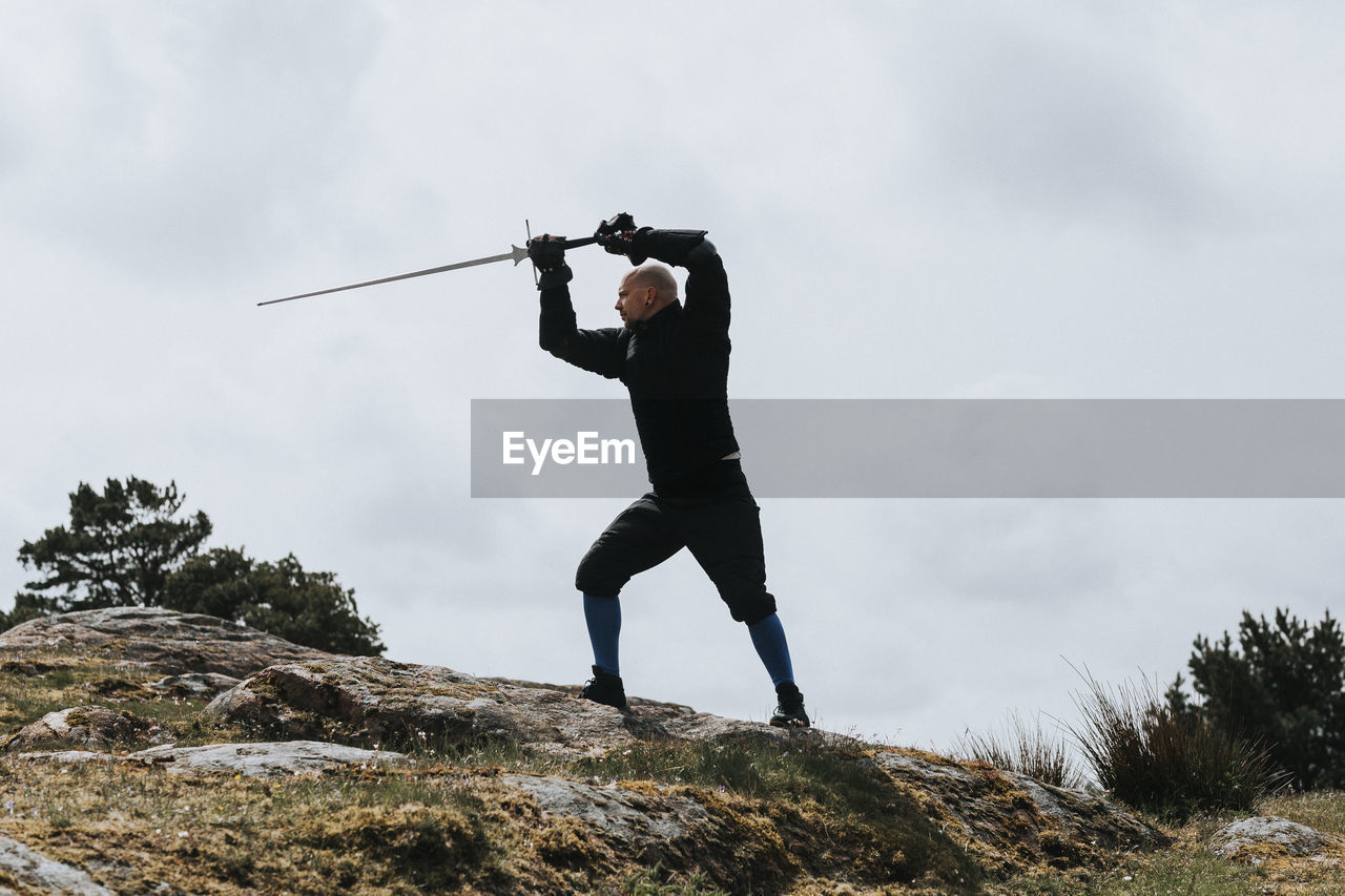 LOW ANGLE VIEW OF MAN HOLDING ROCK