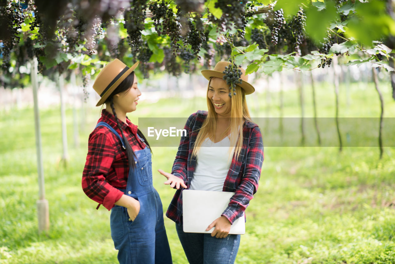 two people, young adult, young women, real people, togetherness, casual clothing, smiling, women, emotion, plant, leisure activity, focus on foreground, happiness, people, lifestyles, three quarter length, hat, adult, nature, standing, couple - relationship, positive emotion
