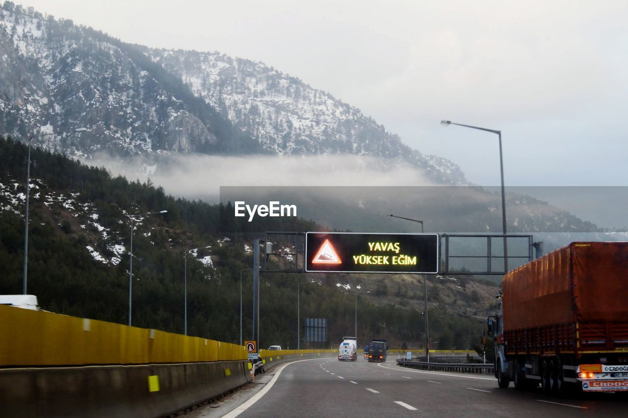 ROAD SIGN ON MOUNTAIN AGAINST SKY