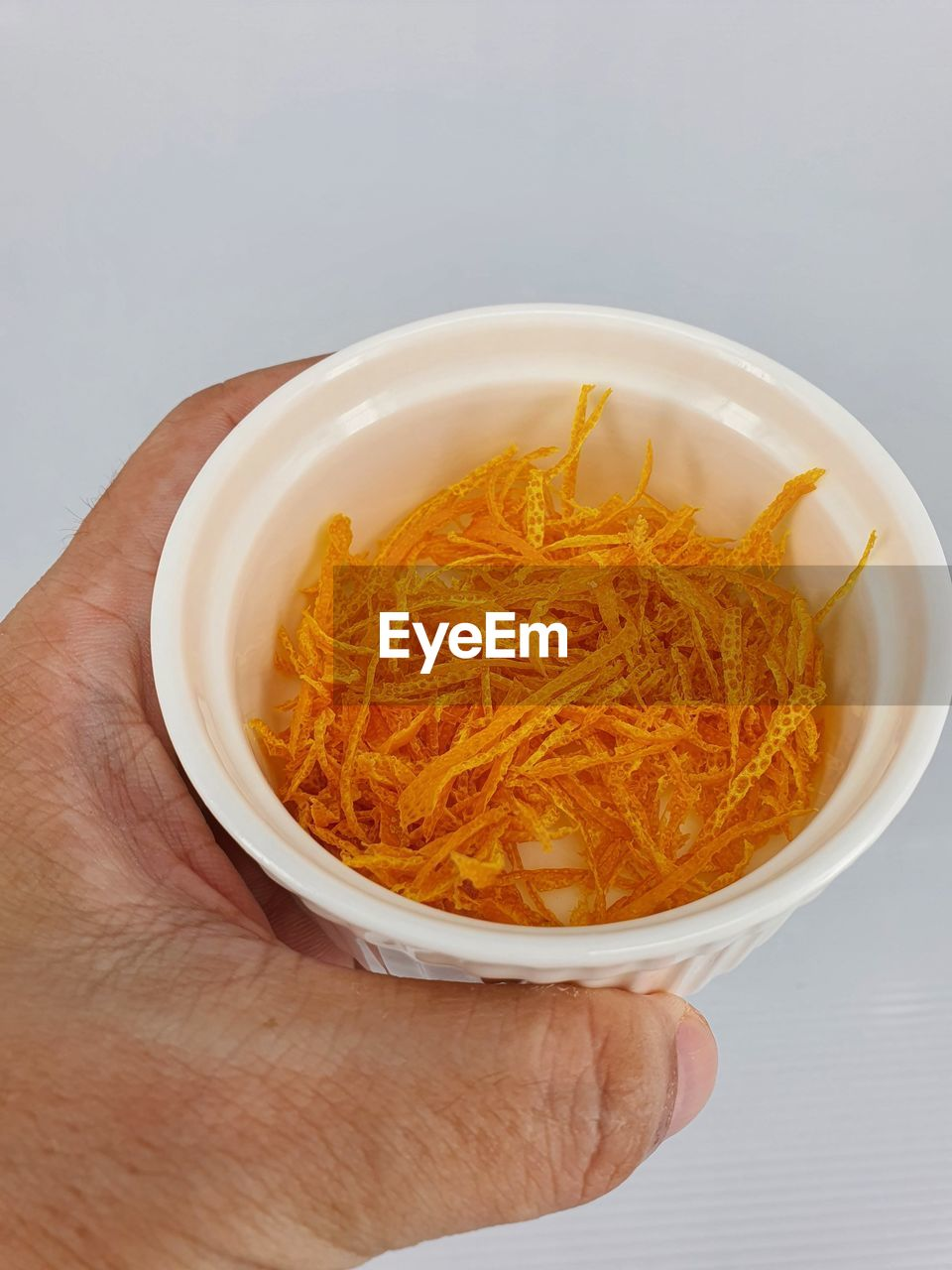 CLOSE-UP OF HAND HOLDING BOWL OF NOODLES