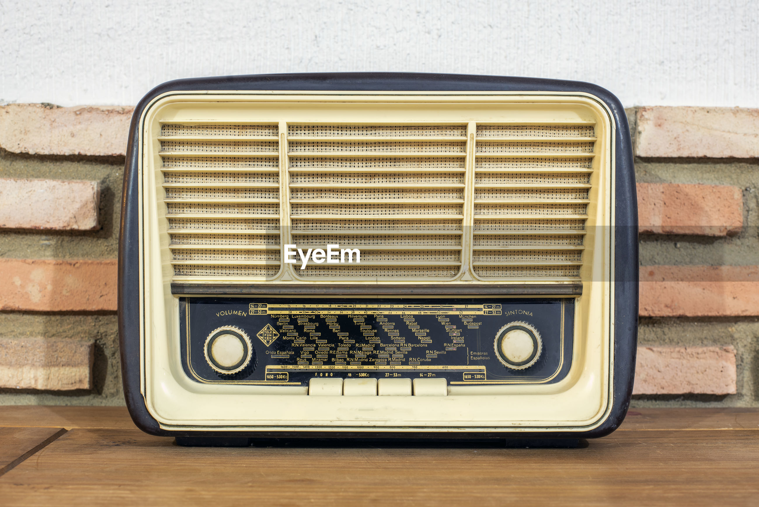 Close-up of vintage radio on table against wall