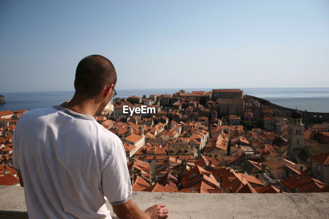 Rear View Of Man Standing By Townscape At Sea Shore Against Clear Sky
