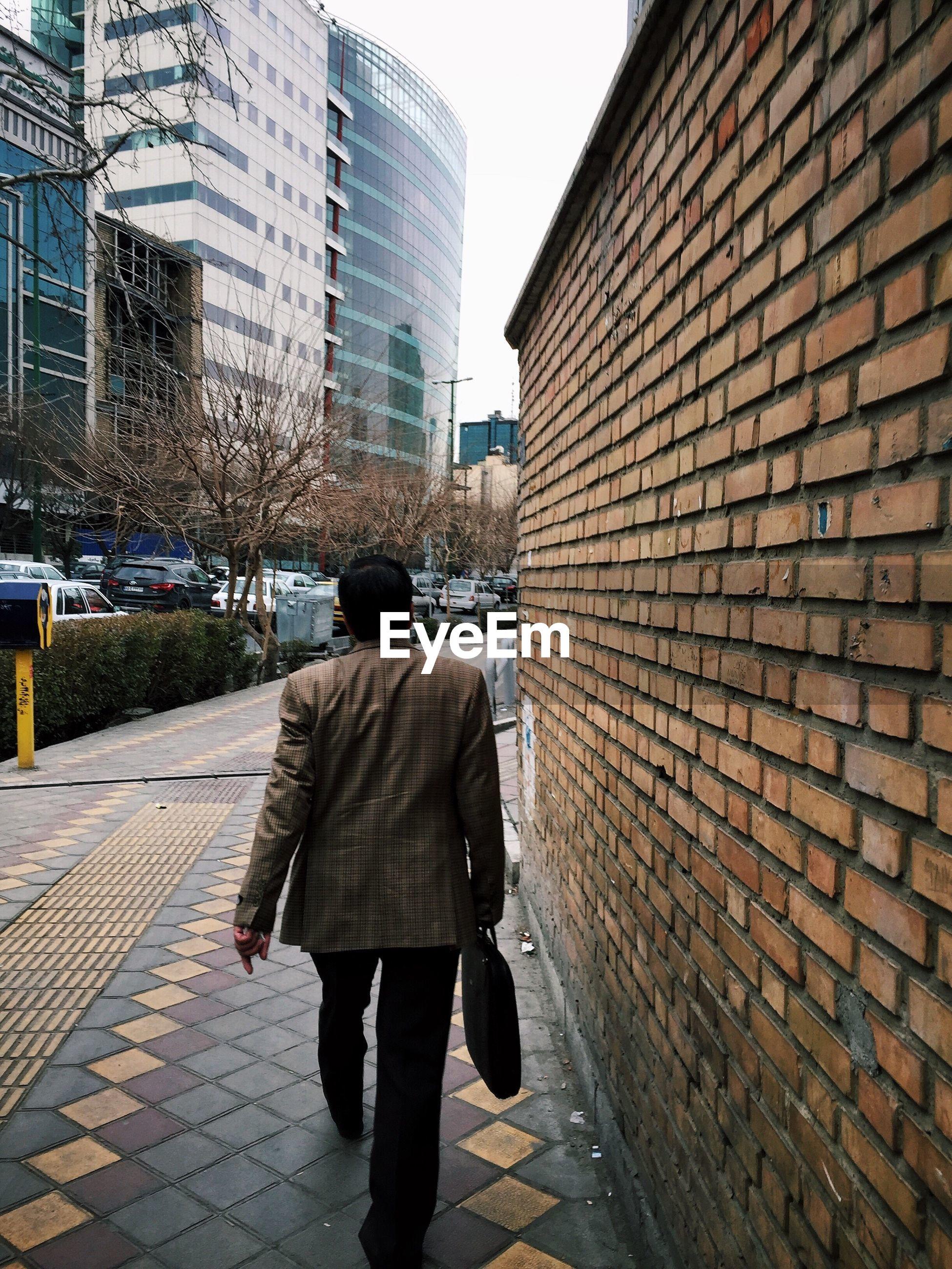 FULL LENGTH REAR VIEW OF MAN WALKING ON ROAD