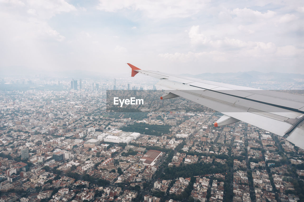Cropped Image Of Airplane Flying Over Cityscape