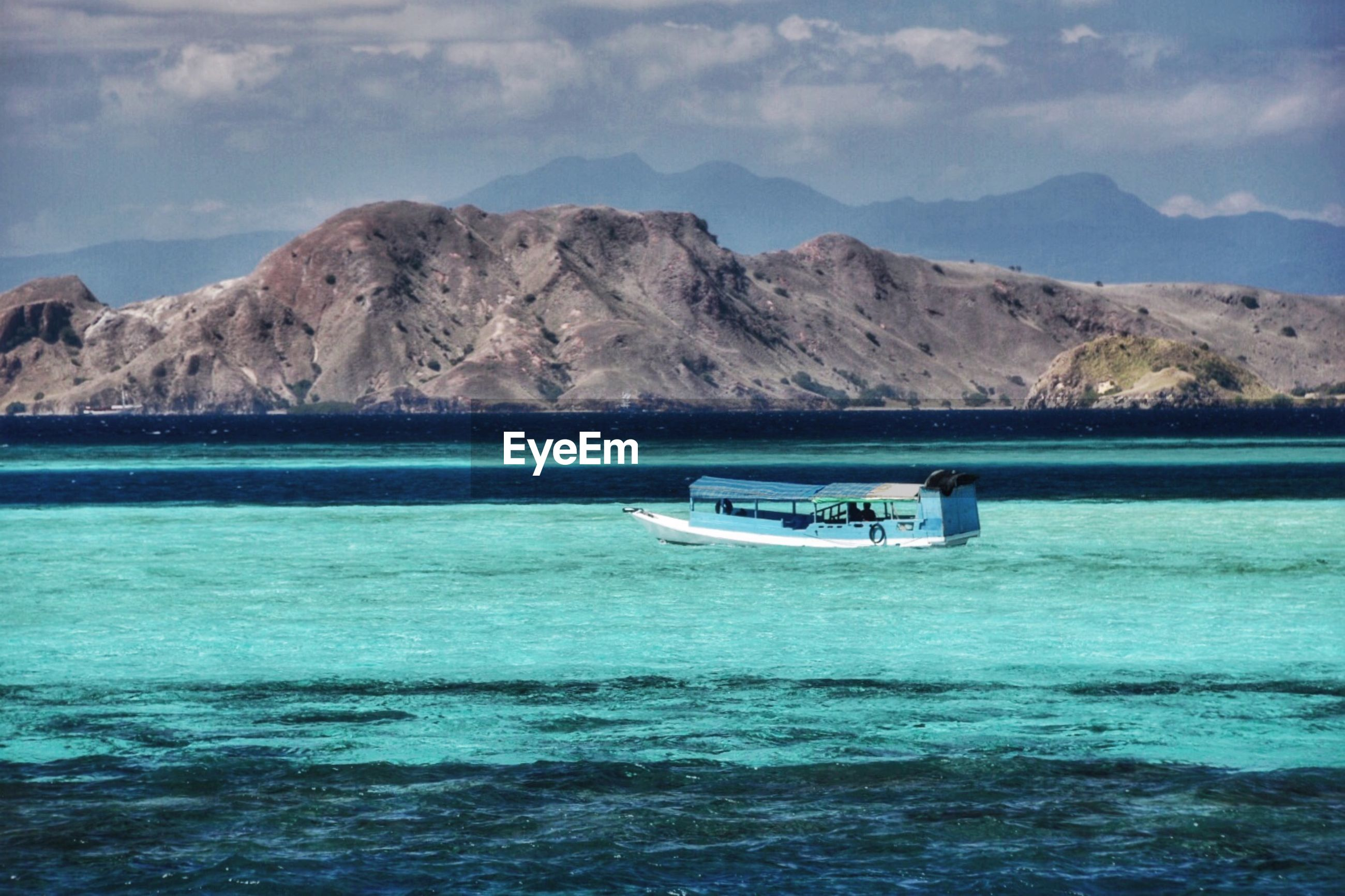 BOAT IN SEA AGAINST MOUNTAINS