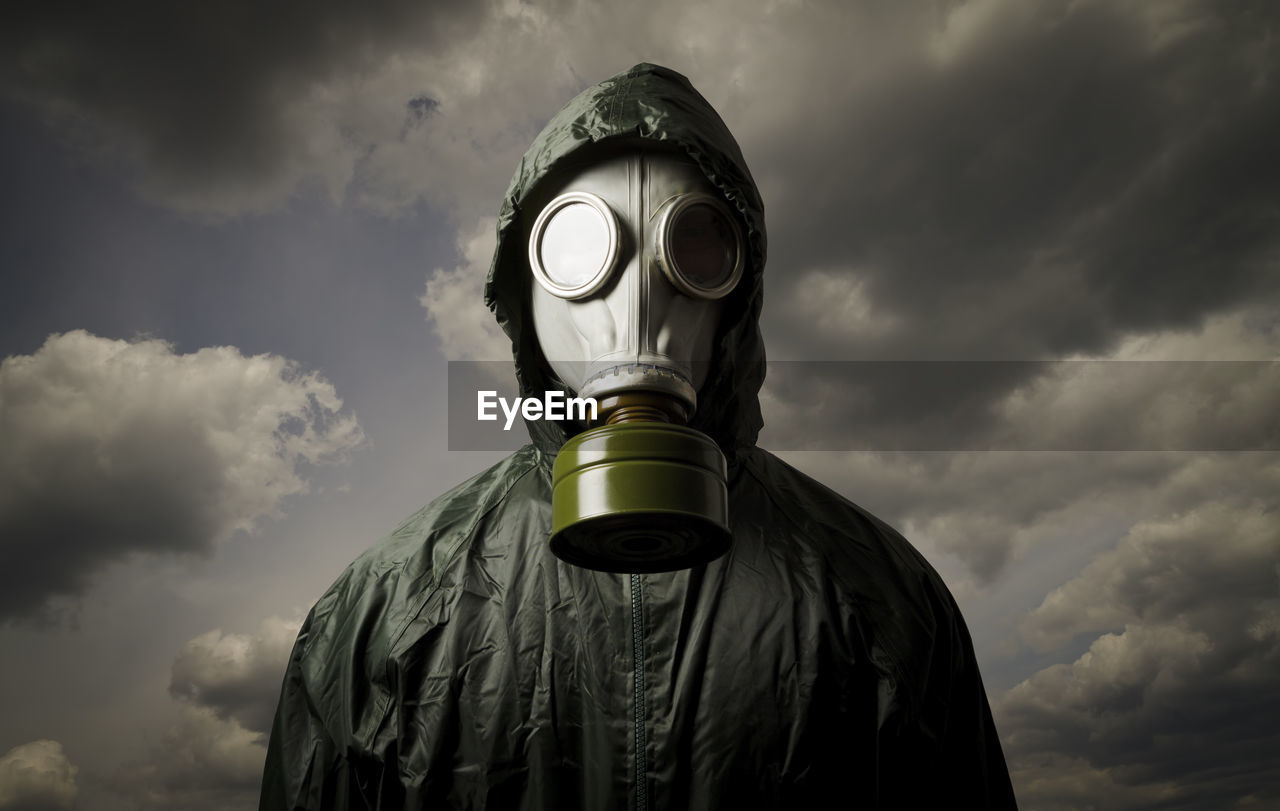 Portrait of person wearing gas mask while standing against cloudy sky