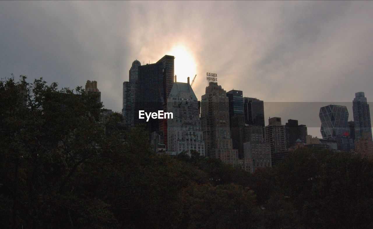 Low Angle View Of Buildings And Trees Against Cloudy Sky At Sunset