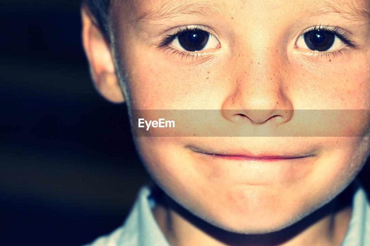 Close-up portrait of cute smiling boy against black background