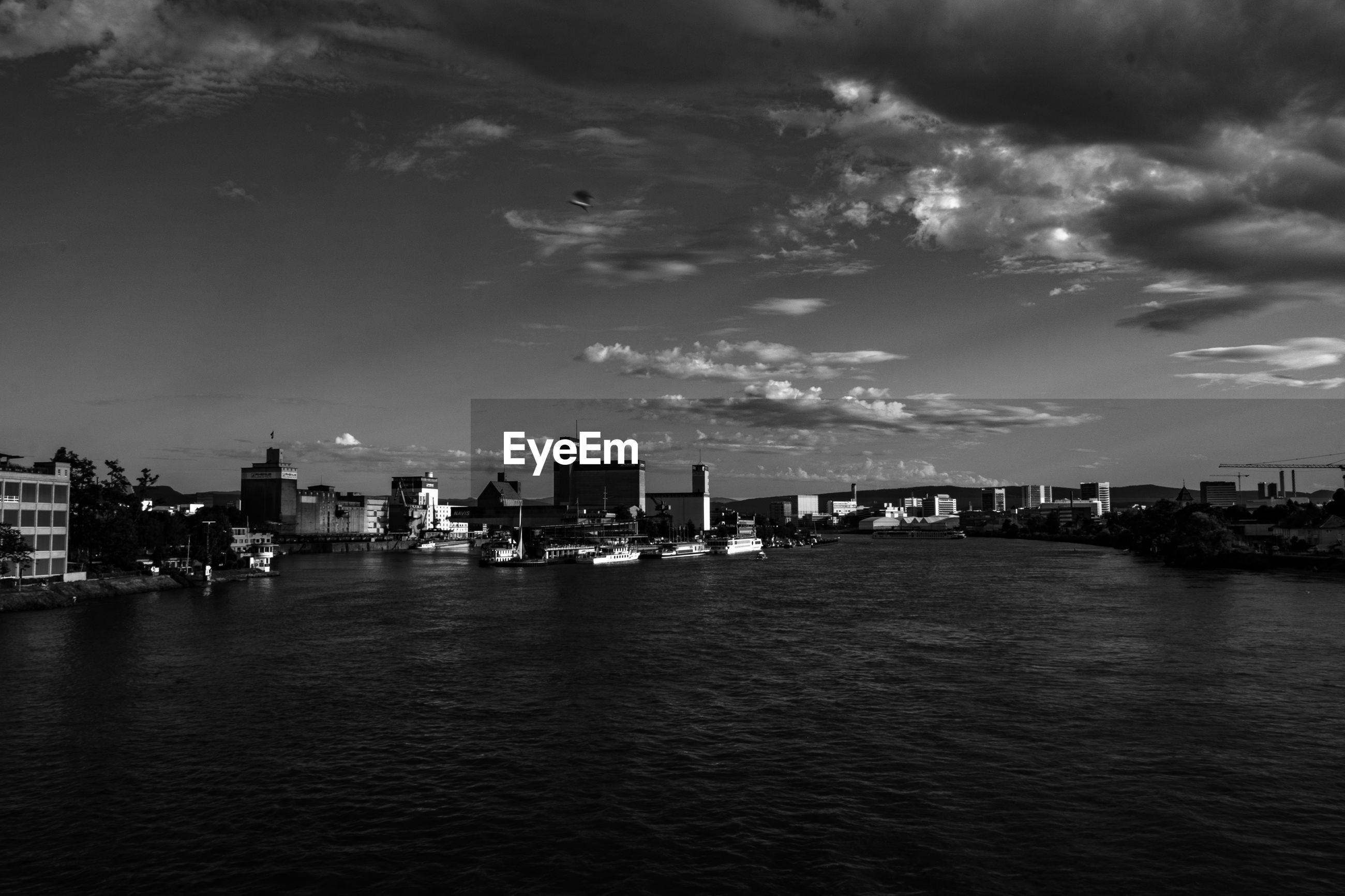 Boats in rhine river at weil am rhein against sky