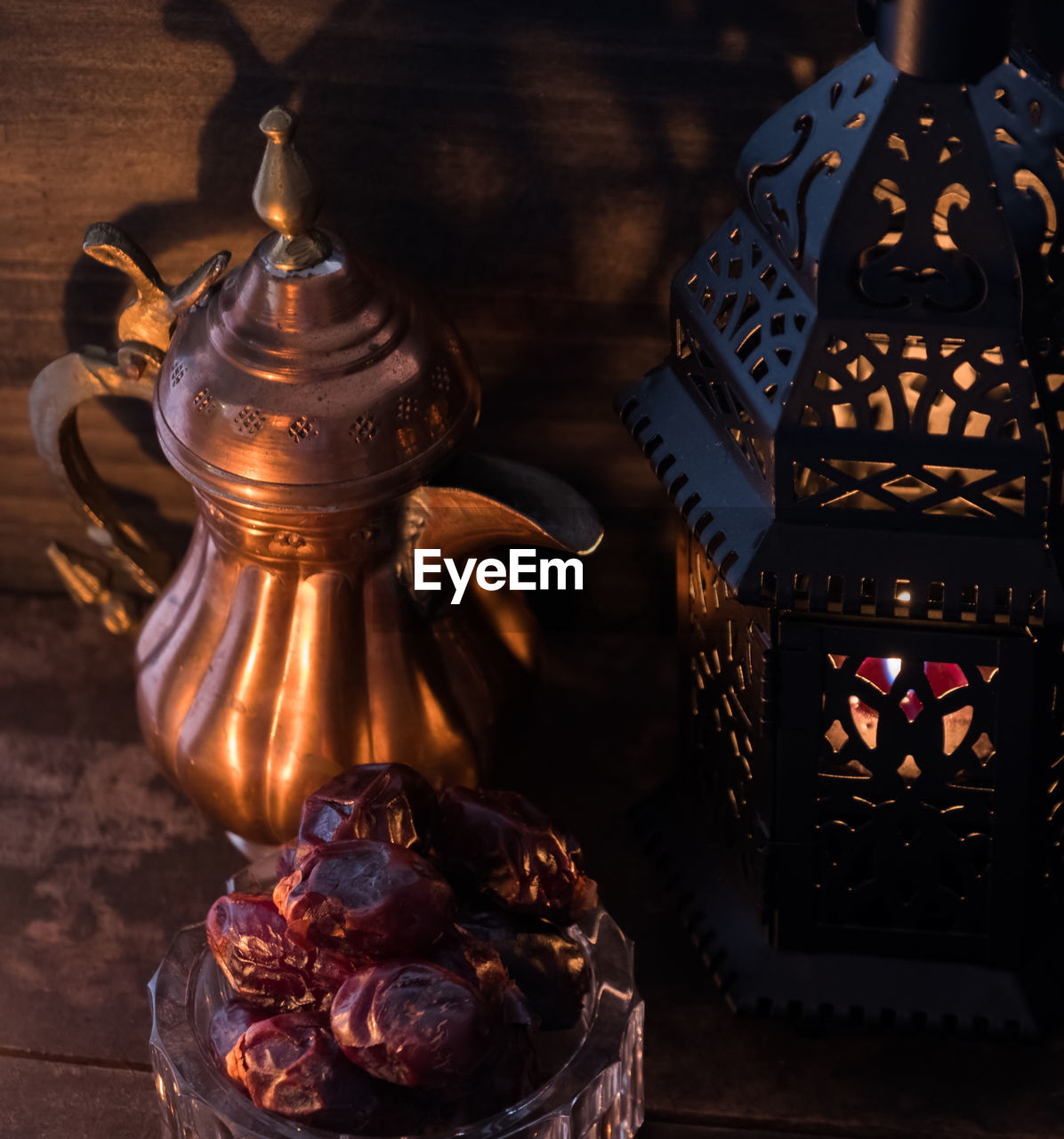 High angle view of antique teapot and lantern with raisins on table