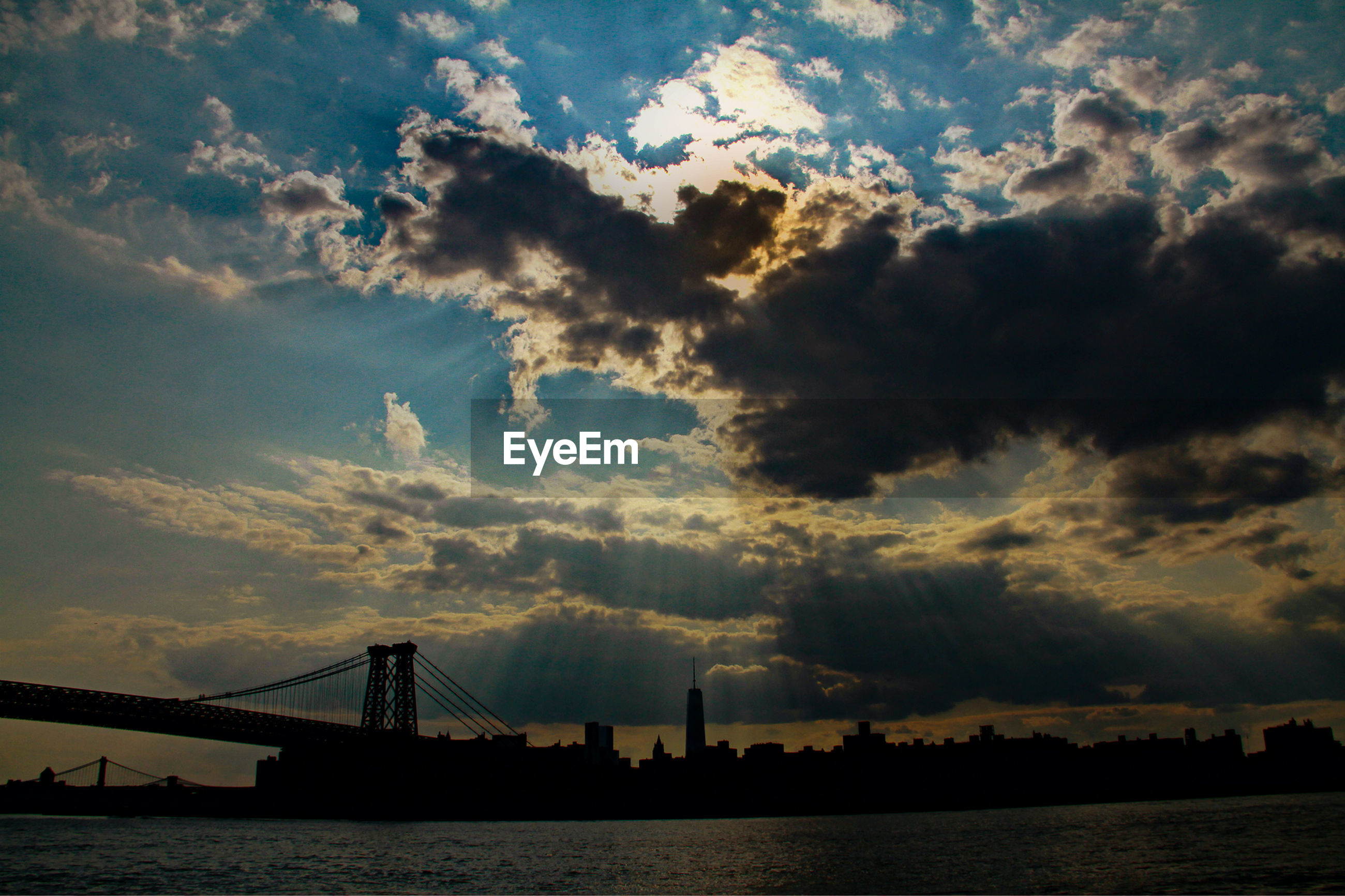 Low angle view of silhouette williamsburg bridge over sea against cloudy sky in city