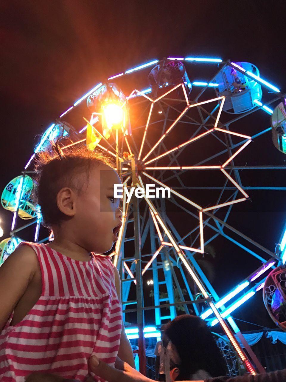 Cute Girl Against Ferris Wheel At Night