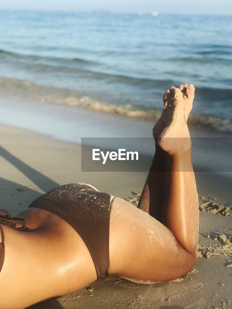 beach, land, sea, water, lying down, one person, relaxation, sand, barefoot, nature, focus on foreground, lifestyles, leisure activity, day, real people, young adult, human leg, outdoors