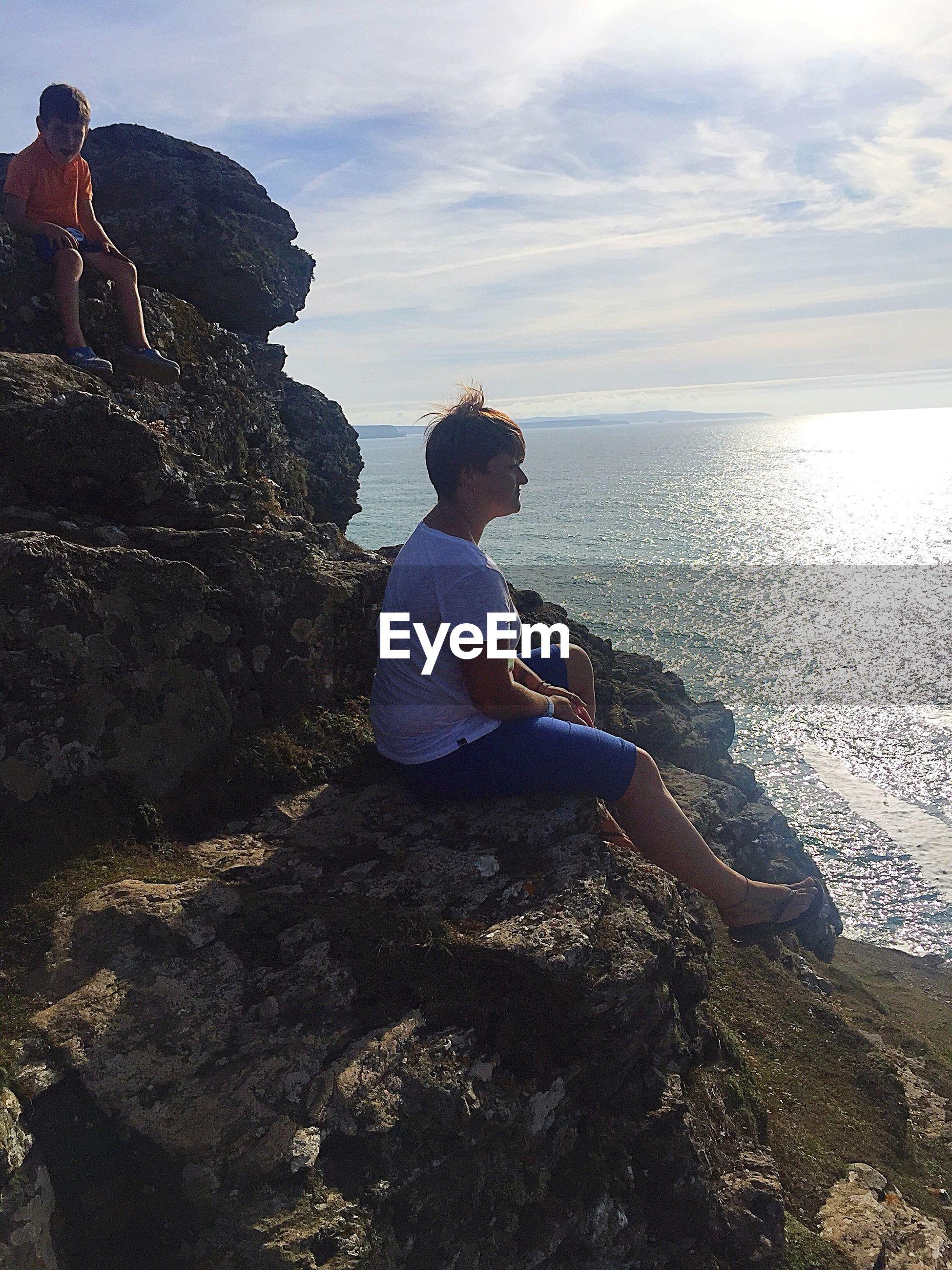 People friends sitting on rock by sea against sky