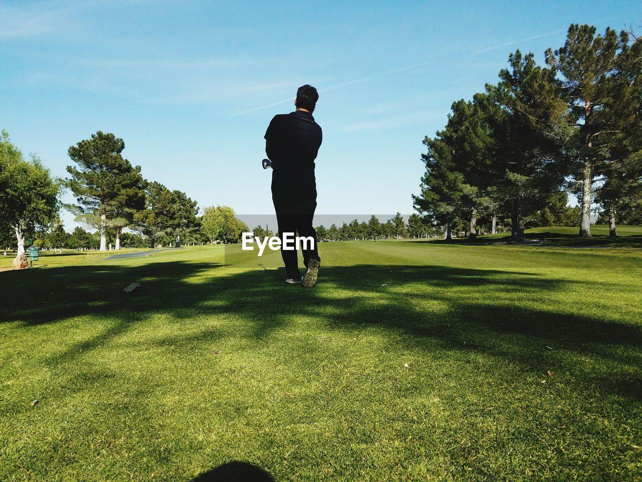 Rear View Of Golfer Walking On Field