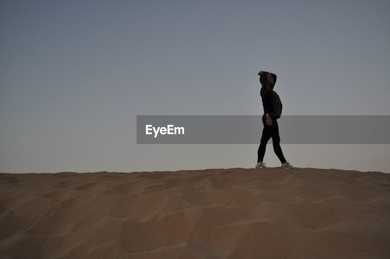 Full length of woman standing on landscape against clear sky