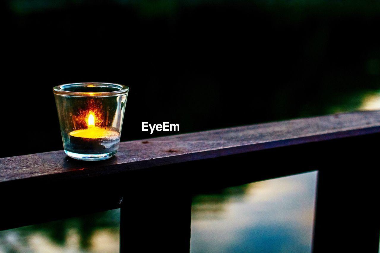 Illuminated tea light candle on railing at dusk