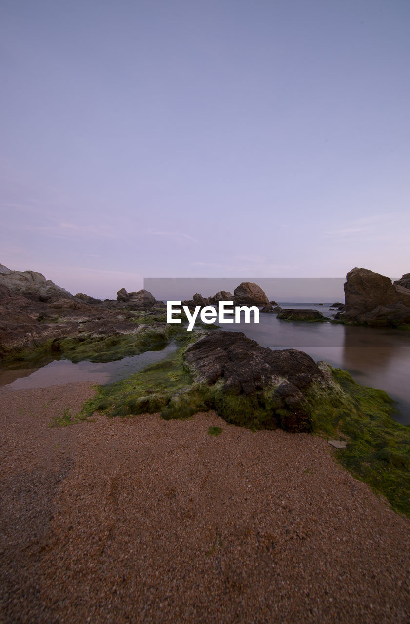 sky, water, beauty in nature, scenics - nature, tranquility, tranquil scene, nature, rock, land, no people, sea, rock - object, solid, non-urban scene, copy space, outdoors, idyllic, sunset, beach