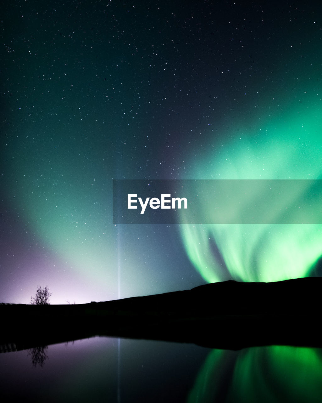 Scenic View Of Aurora Borealis Over Lake Against Sky At Night