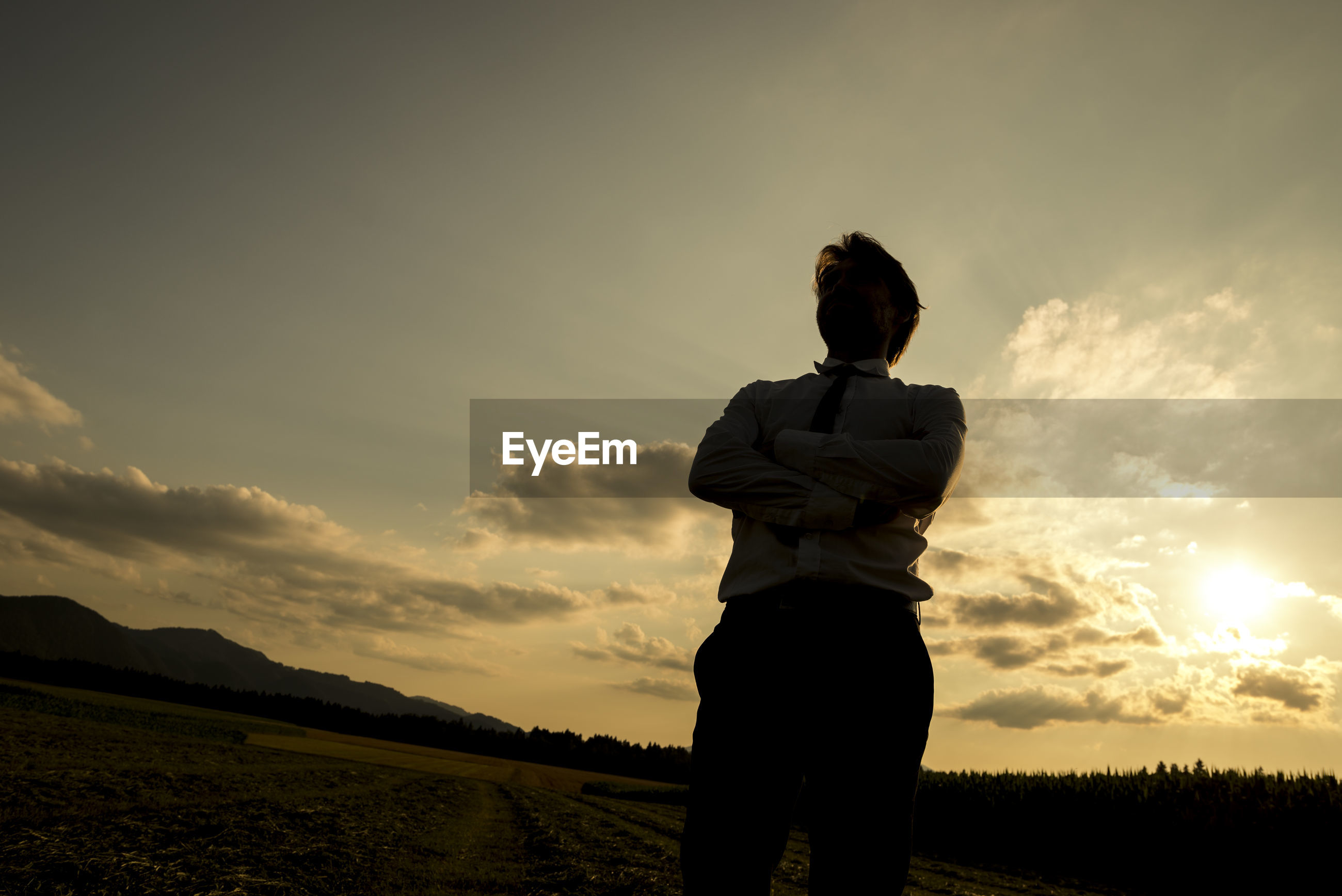 REAR VIEW OF MAN STANDING ON FIELD DURING SUNSET