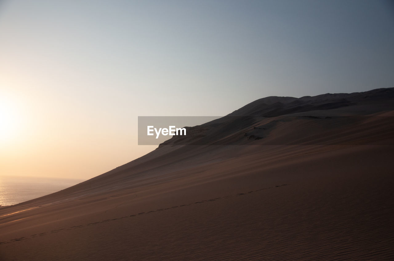 sky, beauty in nature, scenics - nature, tranquility, tranquil scene, sunset, land, non-urban scene, nature, remote, idyllic, sand, water, no people, copy space, sea, mountain, horizon, environment, outdoors, arid climate, climate