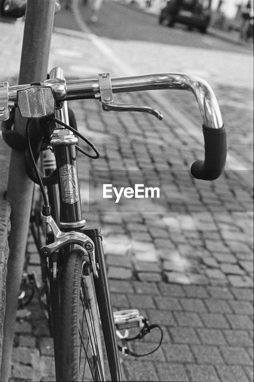 bicycle, land vehicle, transportation, mode of transportation, focus on foreground, metal, stationary, day, no people, street, city, handlebar, security, close-up, outdoors, safety, footpath, protection, parking, handle, wheel