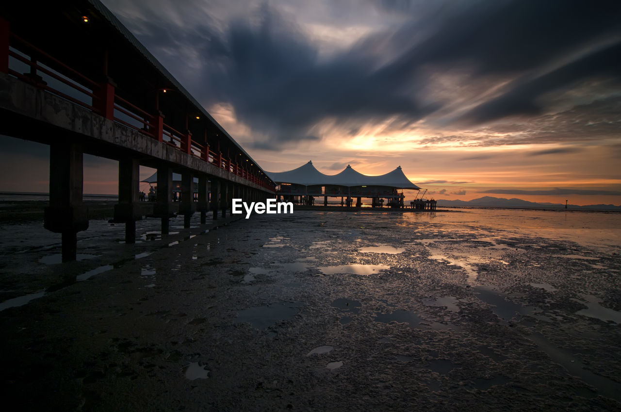 sunset, sea, sky, beach, cloud - sky, water, outdoors, nature, sand, built structure, tranquility, scenics, architecture, no people, beauty in nature, horizon over water, day