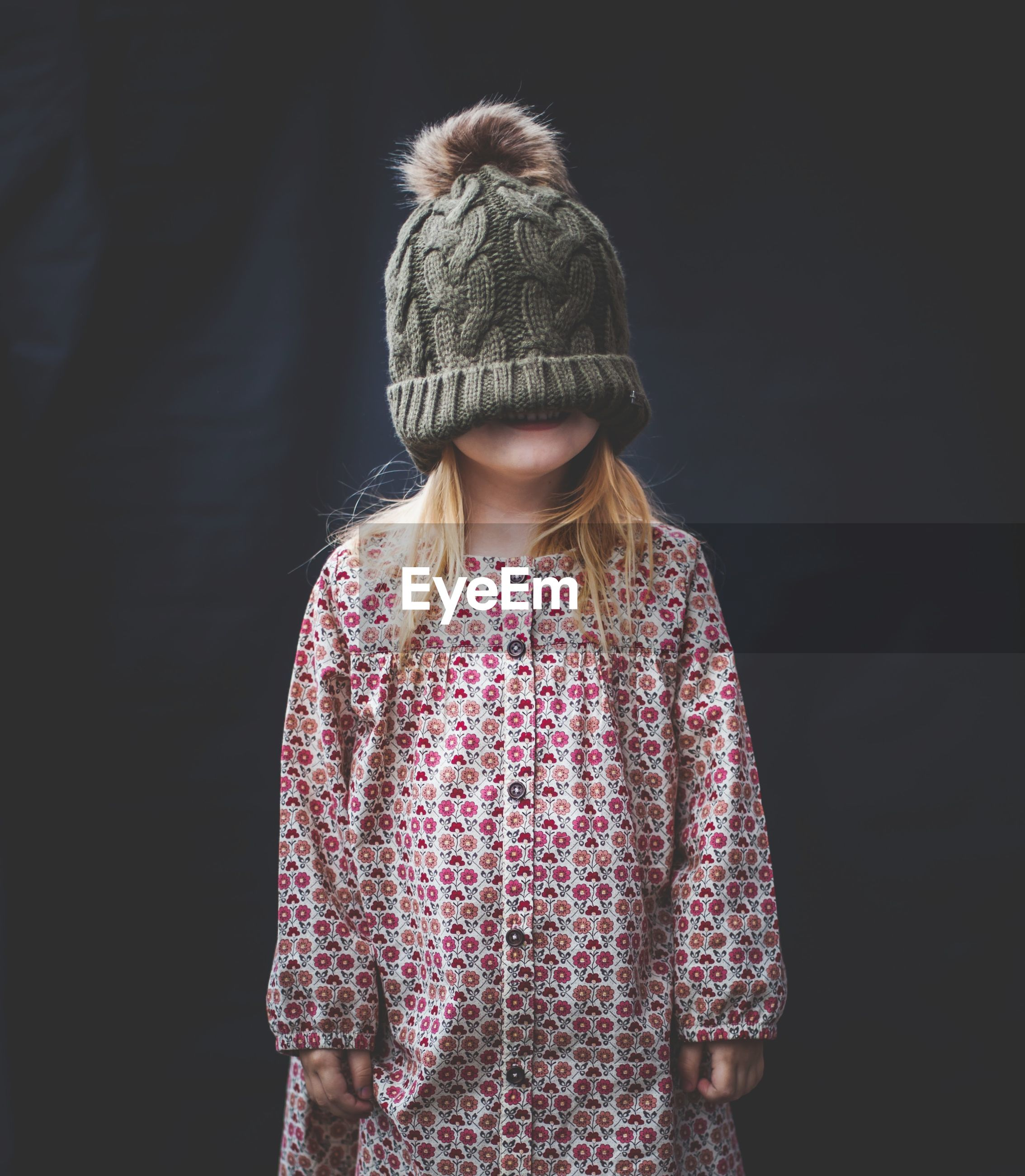 Girl wearing knit hat while standing against black background
