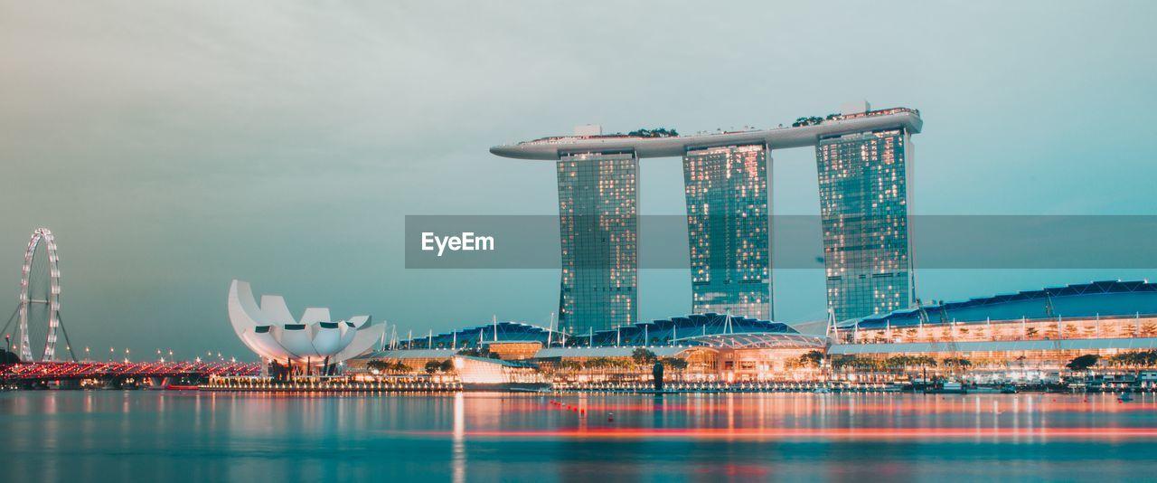 Illuminated City Buildings Against Sky