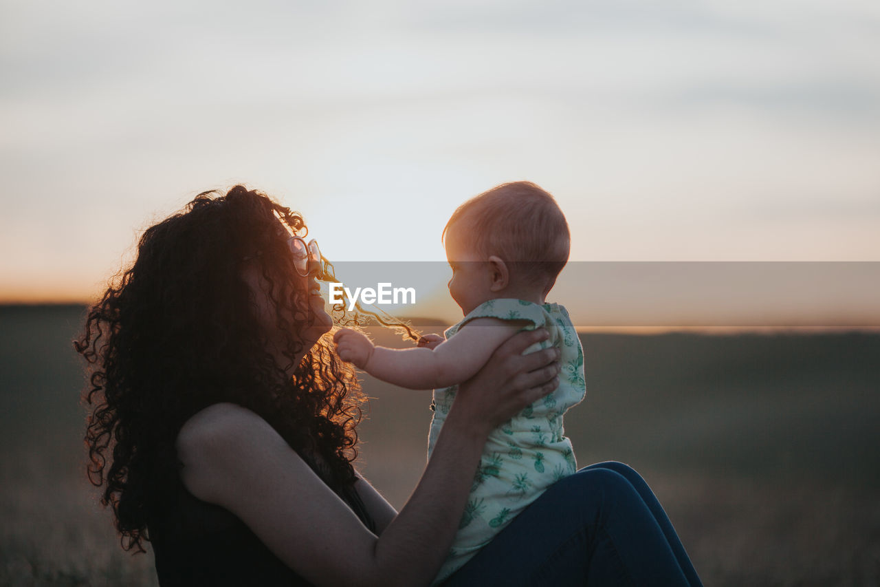 Side View Of Woman With Baby Sitting On Field During Sunset