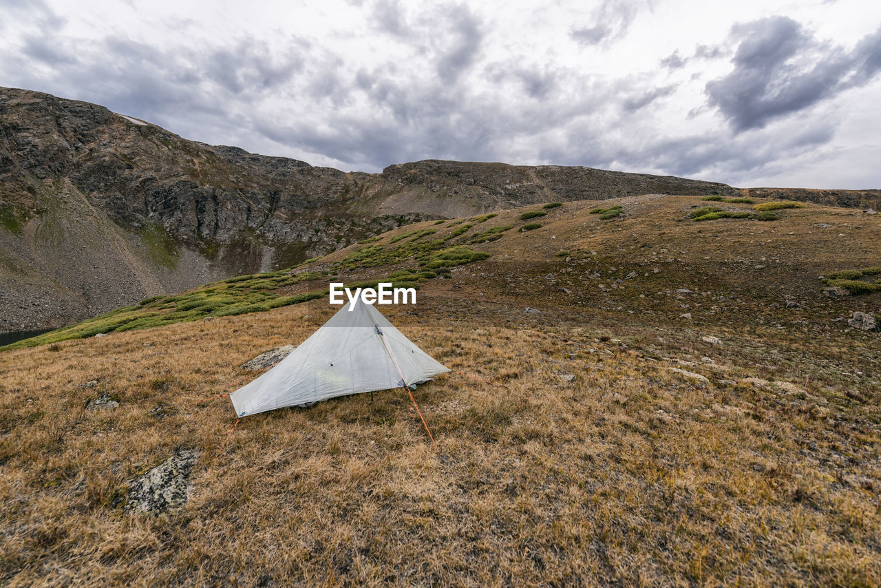 TENT ON FIELD AGAINST MOUNTAIN