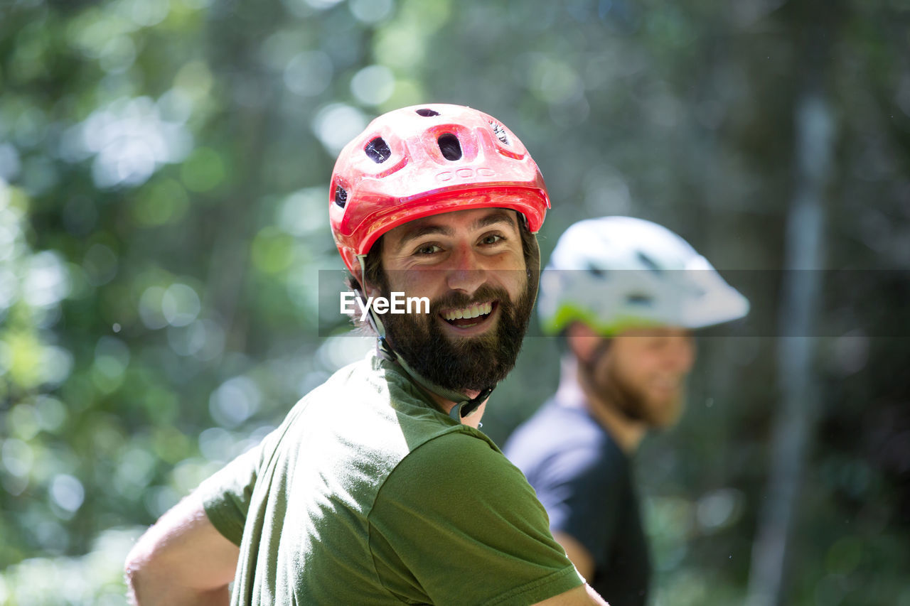 portrait, smiling, real people, focus on foreground, helmet, headshot, looking at camera, leisure activity, lifestyles, young adult, headwear, young men, men, emotion, adult, happiness, day, beard, people, facial hair, outdoors