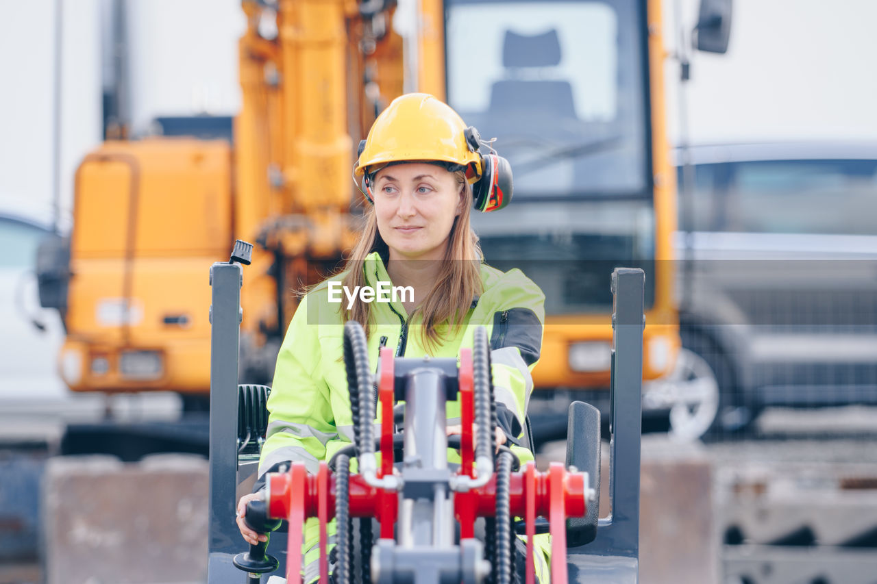 Woman With Machinery At Construction Site