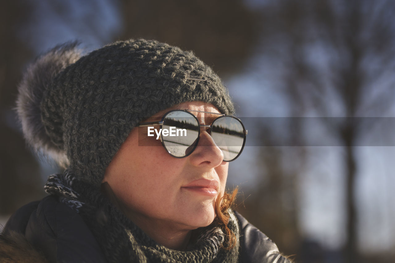 Close-Up Of Woman In Warm Clothing Wearing Sunglasses Against Bare Trees