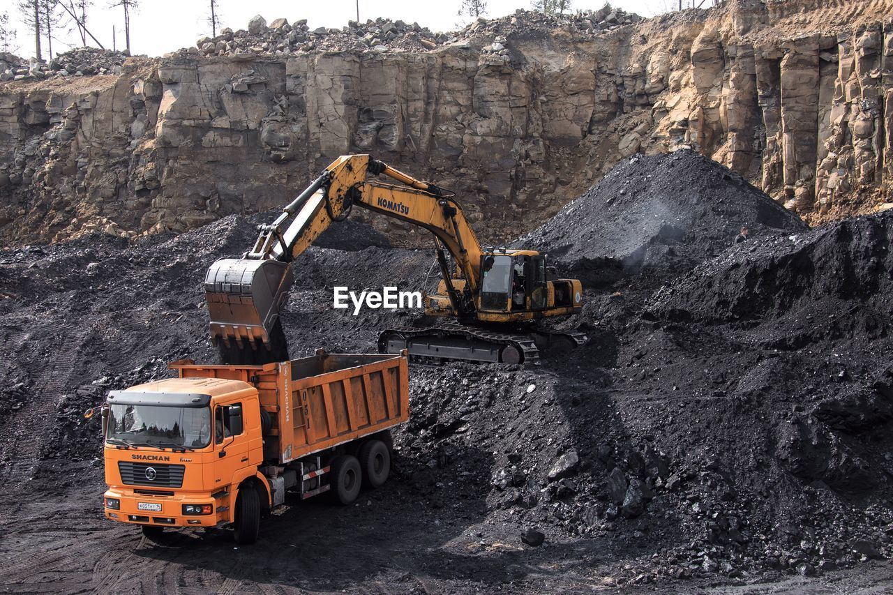 transportation, construction machinery, mode of transportation, land vehicle, industry, earth mover, construction industry, bulldozer, digging, quarry, machinery, construction site, rock, rock - object, truck, commercial land vehicle, day, mining, nature, development, construction vehicle, outdoors, construction equipment, mud