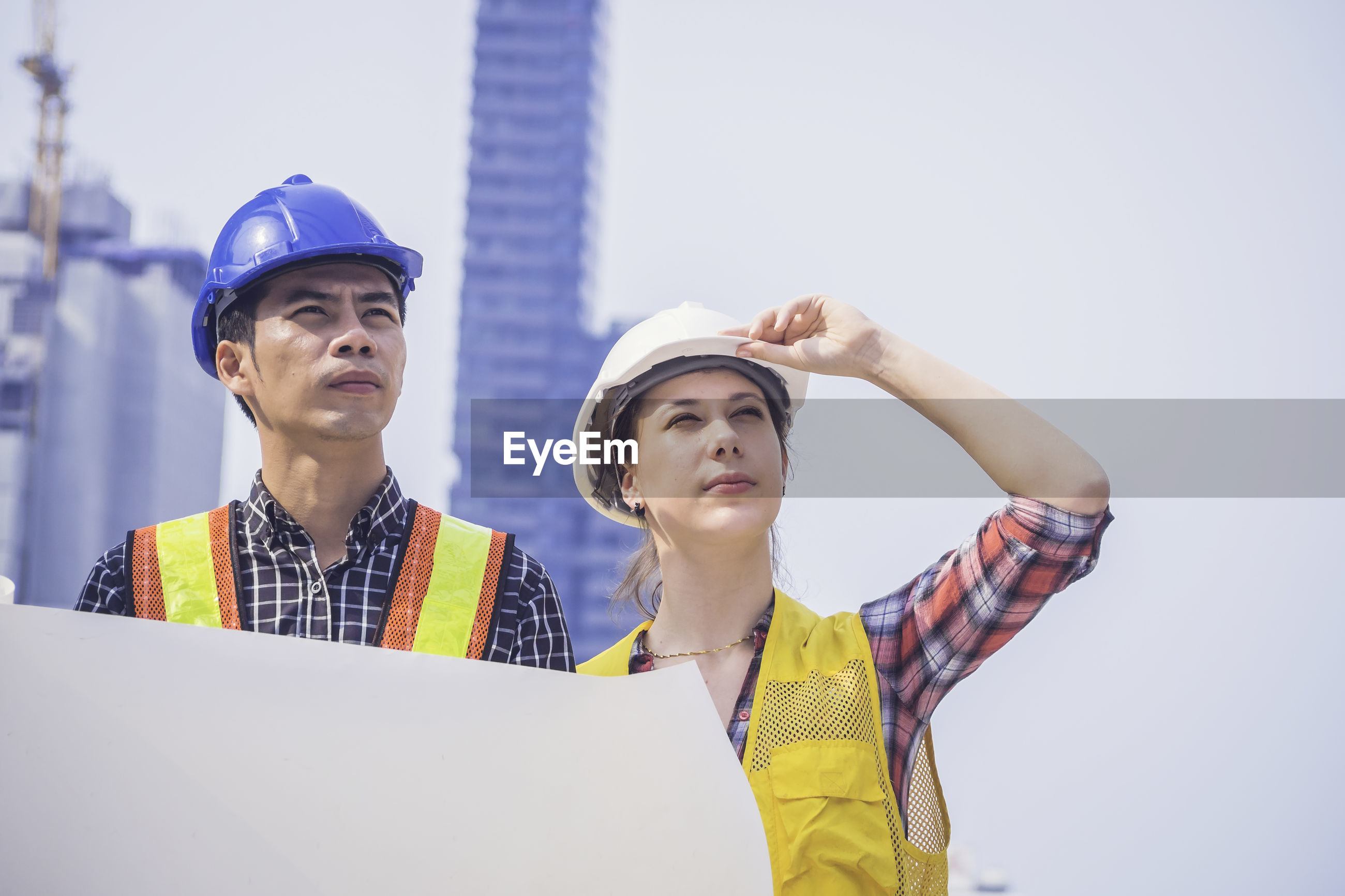 Two engineers discussing over blueprint while standing outdoors
