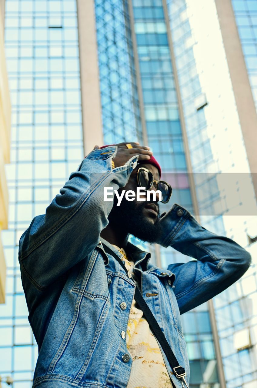 one person, real people, architecture, built structure, lifestyles, building exterior, day, leisure activity, casual clothing, city, glasses, waist up, standing, focus on foreground, fashion, young adult, low angle view, sunglasses, jacket, outdoors, office building exterior
