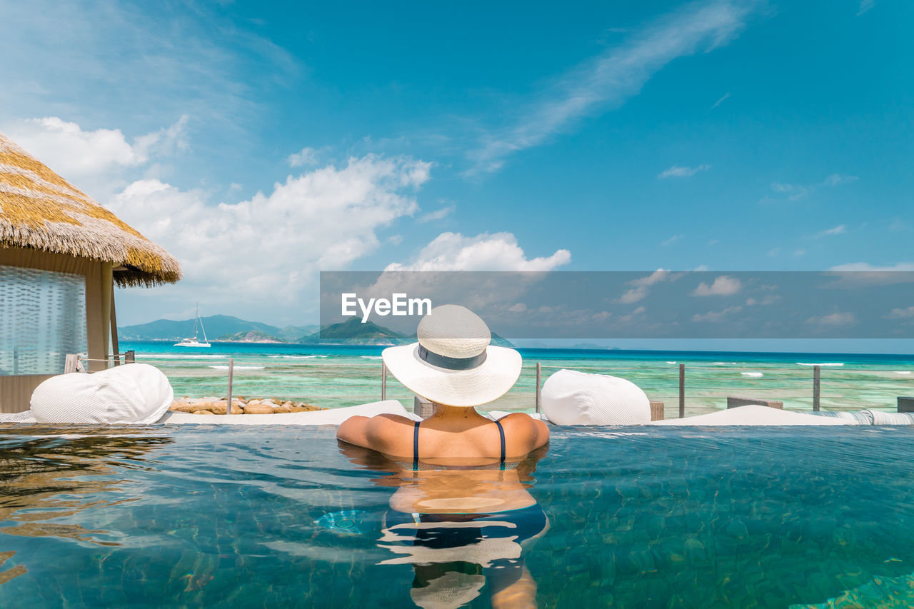 Rear View Of Man In Swimming Pool Against Sea