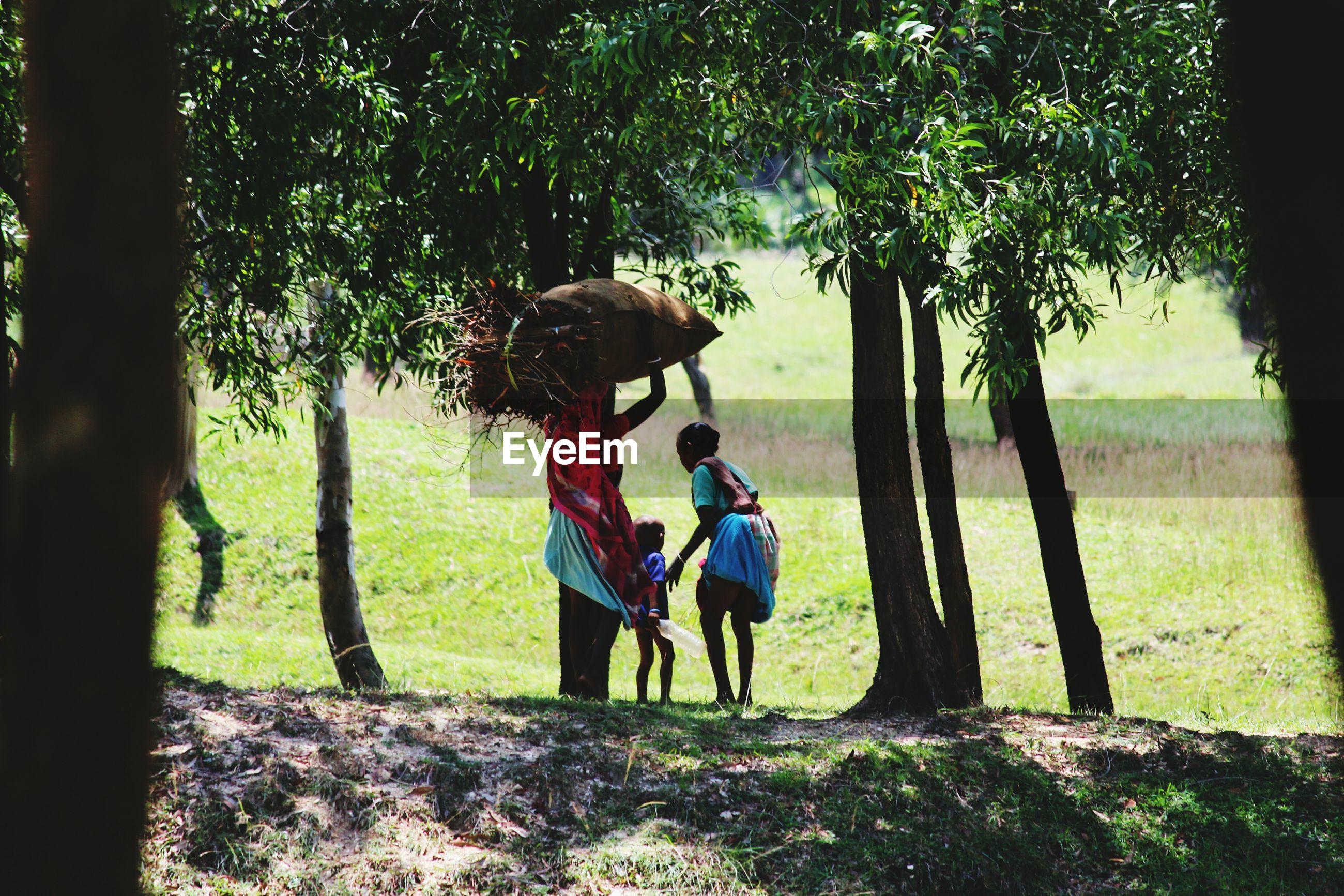 Women with boy standing on field