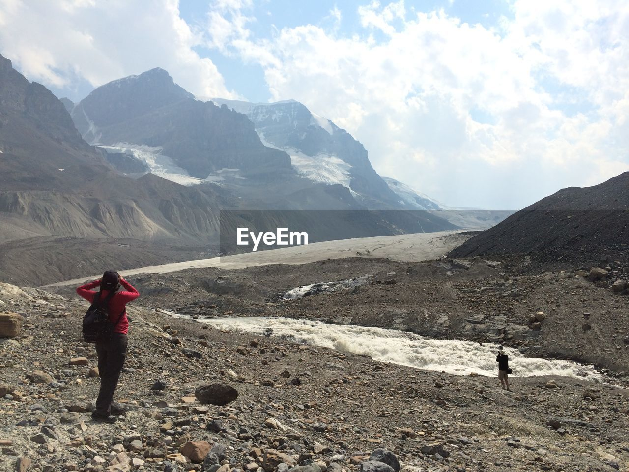 Female Hiker Standing On Mountain Against Cloudy Sky At Athabasca Glacier