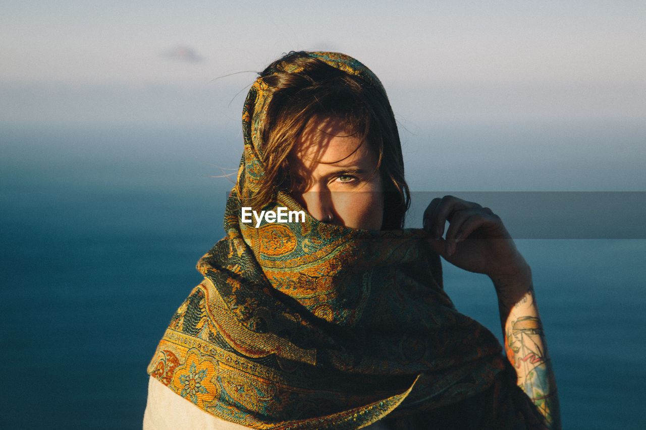 Portrait Of Young Woman Covering Face With Scarf Against Sea