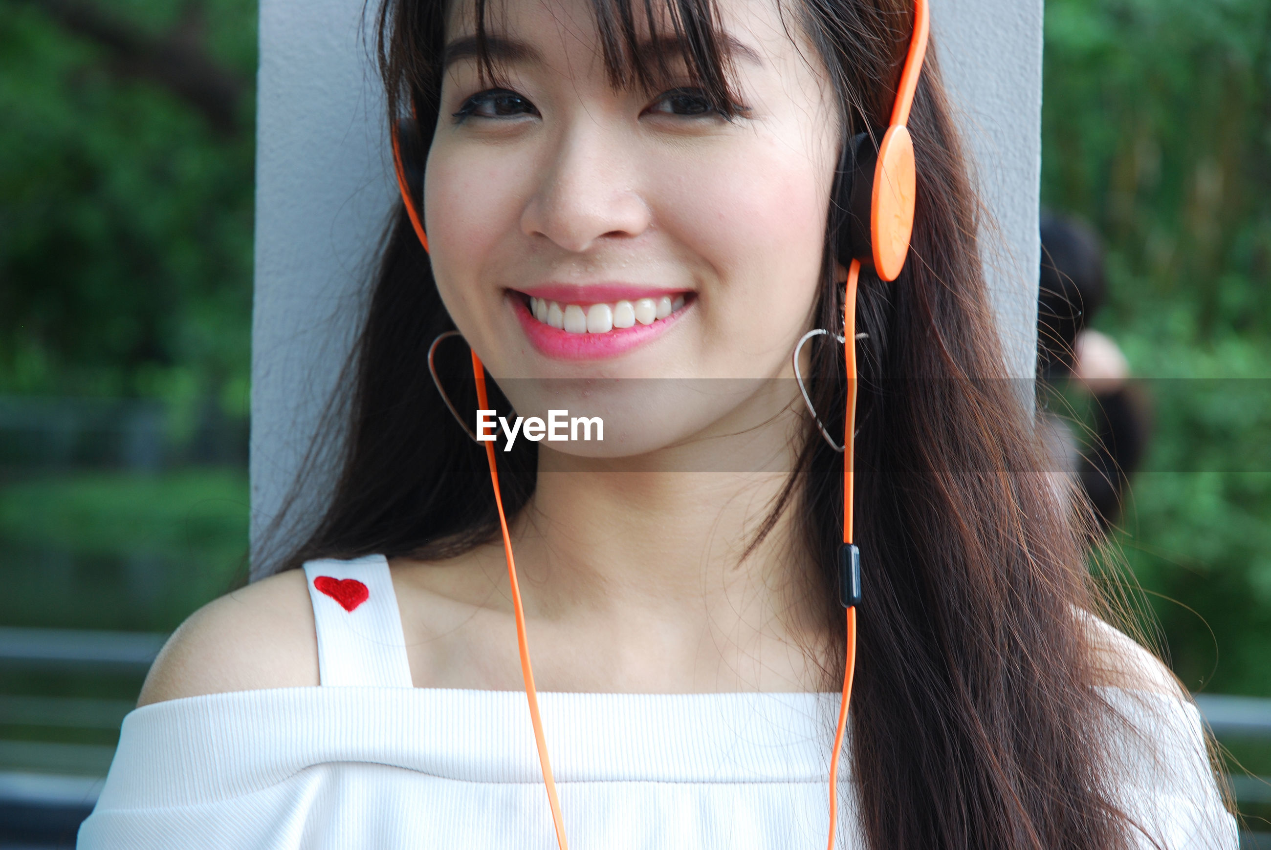 Close-up portrait of smiling young woman listening music on headphones