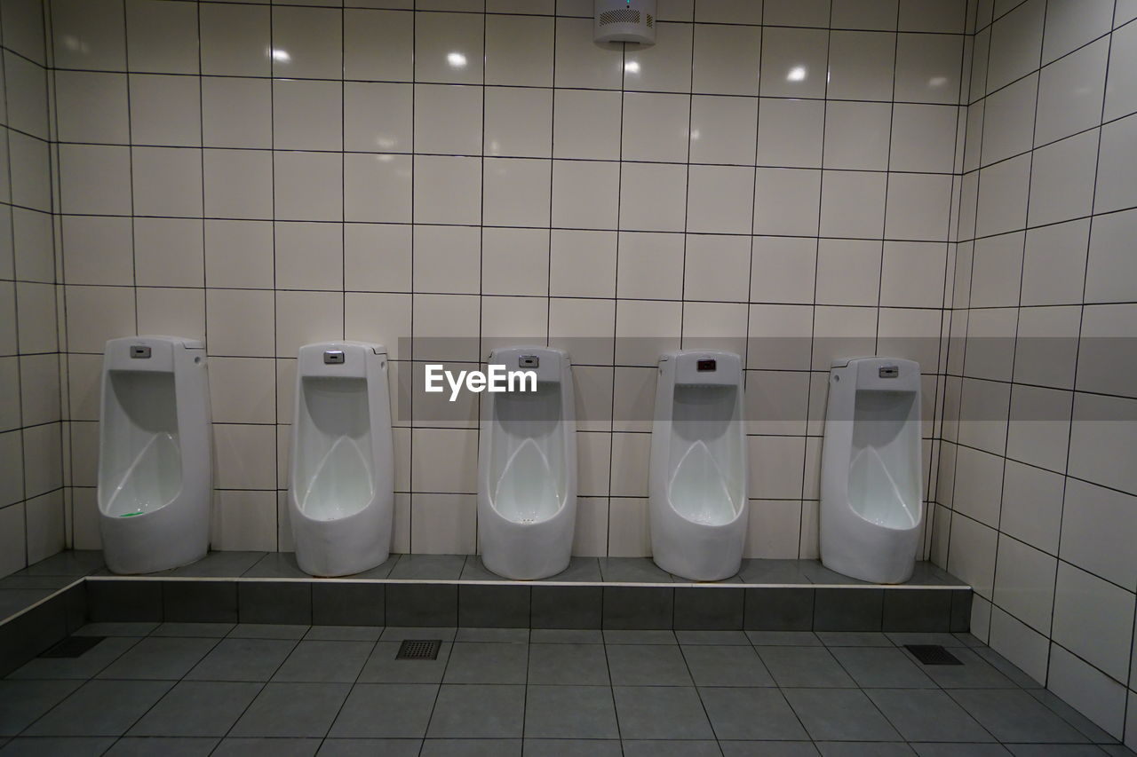 Urinals on tiled wall in public restroom
