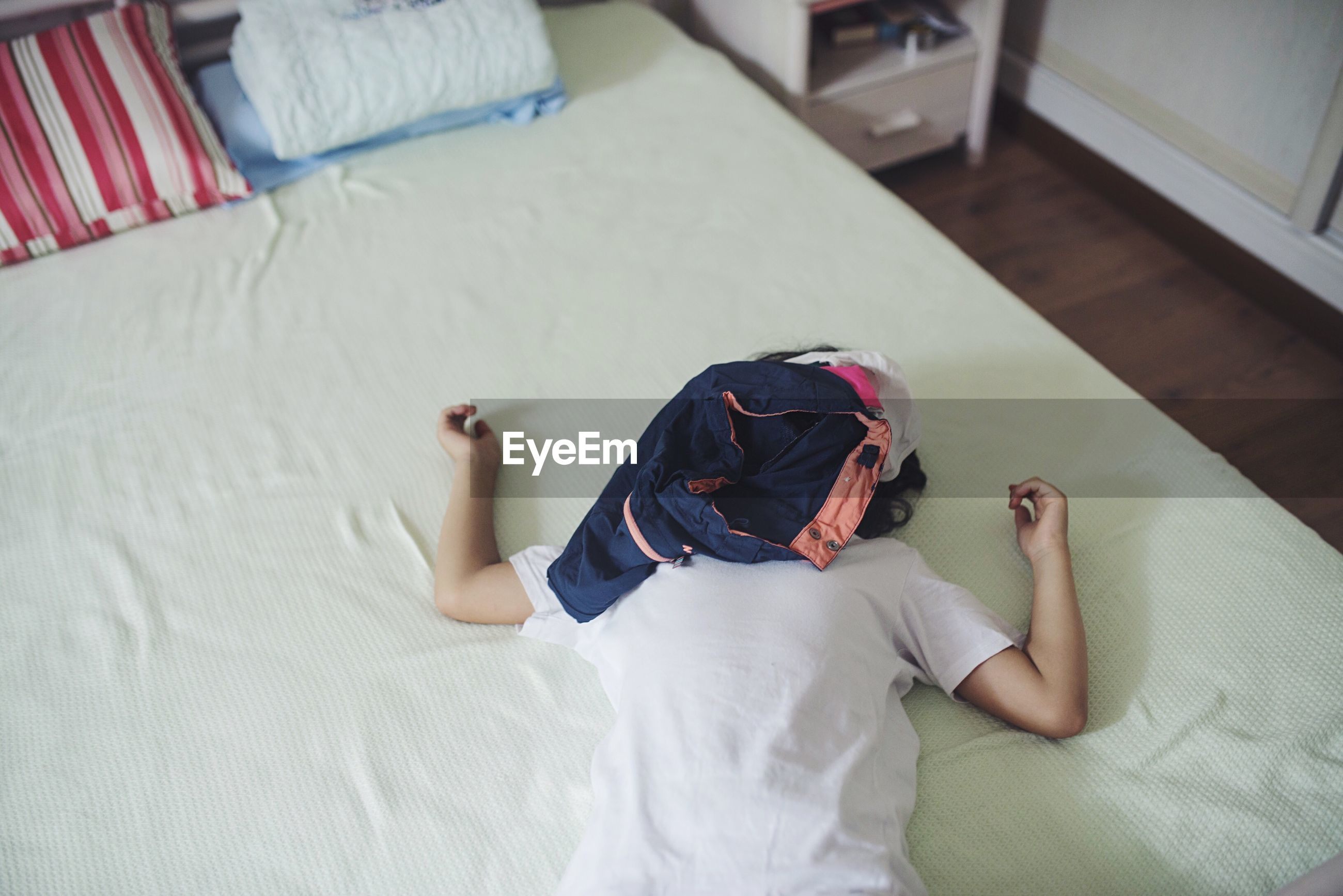 Cloths over man resting on bed at home