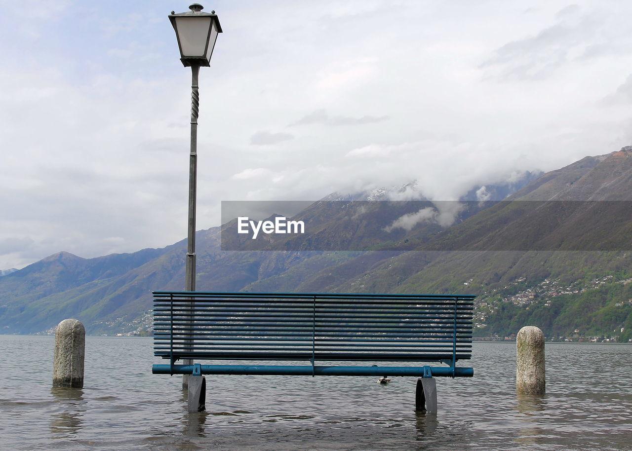Empty Bench Against Mountain Range Against Sky
