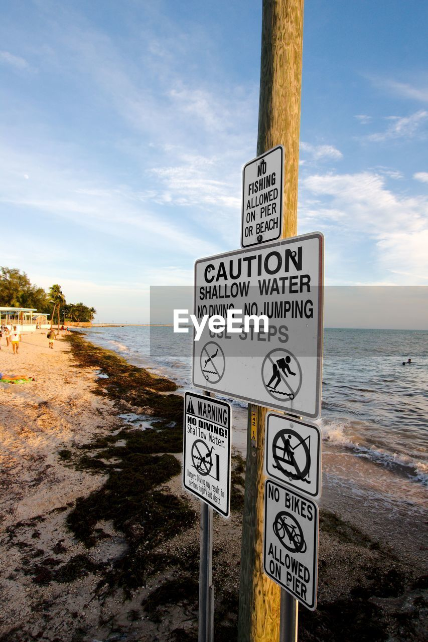 Close-up of warning signs on sea shore against sky