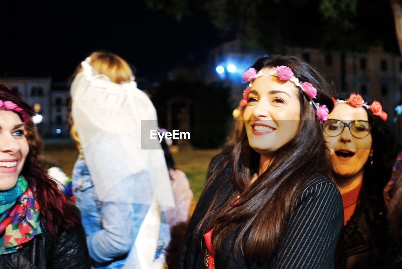 women, lifestyles, real people, leisure activity, adult, happiness, group of people, focus on foreground, event, young women, people, night, young adult, enjoyment, emotion, incidental people, clothing, smiling, togetherness, hair, hairstyle, festival, nightlife, beautiful woman