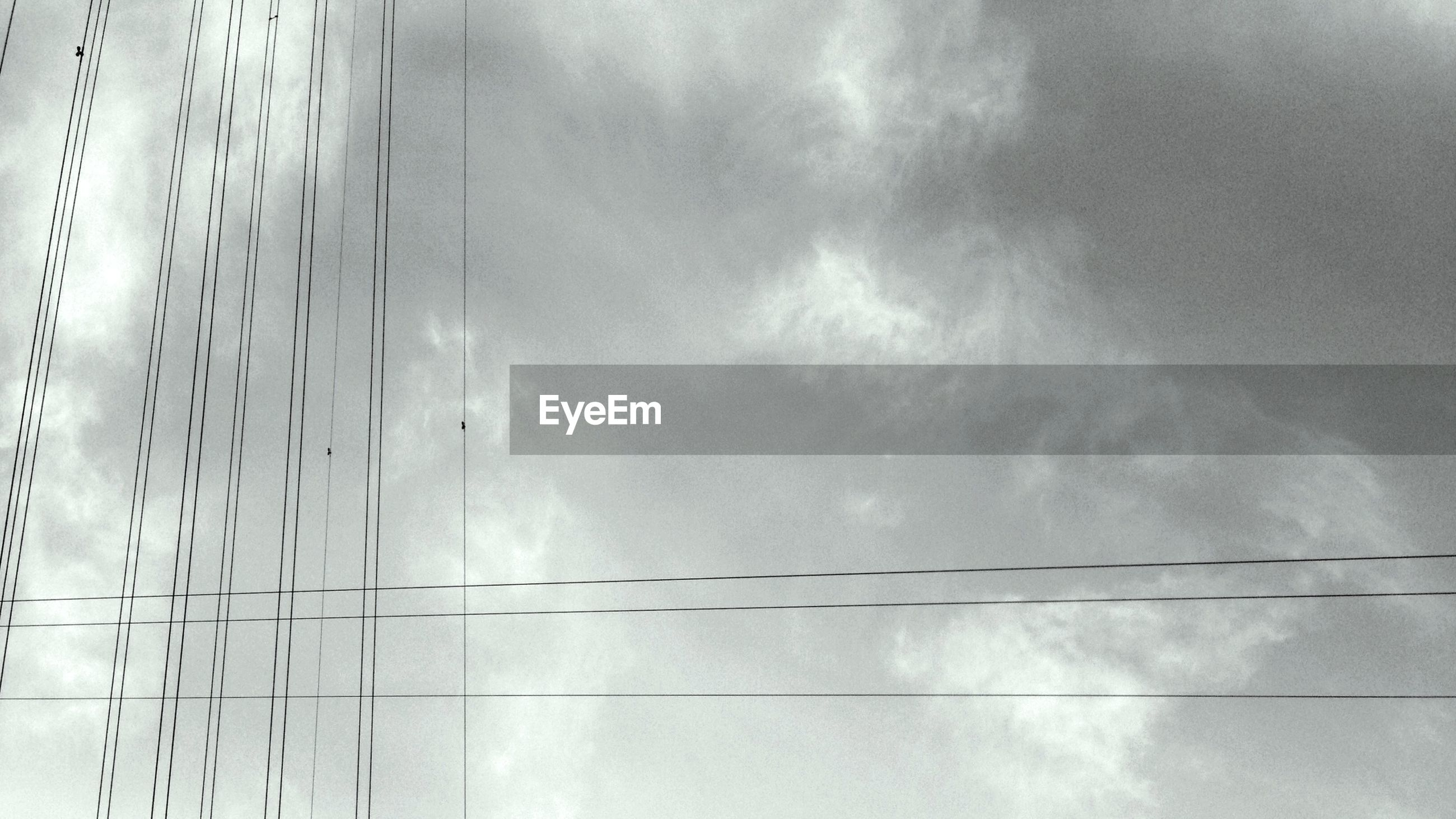 low angle view, sky, cloud - sky, built structure, architecture, cloudy, cloud, building exterior, power line, cable, connection, modern, no people, day, outdoors, electricity, high section, weather, building, overcast